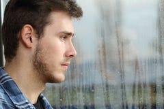 Mannsehnsucht und Schauen durch Fenster Stockbild