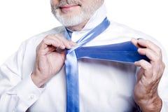 Mannsenior, der angekleidet erhält, windsor Krawatte binden lizenzfreie stockfotografie