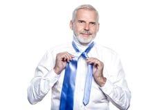 Mannsenior, der angekleidet erhält, windsor Krawatte binden lizenzfreie stockfotos