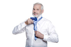 Mannsenior, der angekleidet erhält, windsor Krawatte binden stockbilder