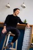 Mannsitzen und -c$lächeln Stockfoto