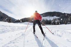 Mannskilanglauf während des sonnigen Wintertages stockbilder