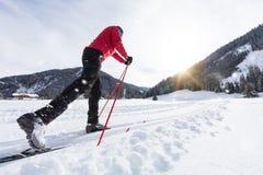 Mannskilanglauf während des sonnigen Wintertages stockfotografie