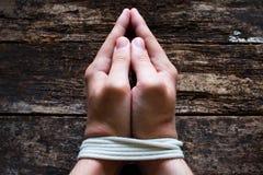 Mannsklave betet mit seinen gebundenen Händen Stockfotografie