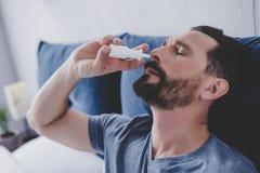Mannsprühtropfen seiner Nase lizenzfreie stockbilder