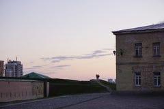 Mannstände des Schattenbildes zwei auf Hügel gegen Abend-Sonnenunterganghimmel des Hintergrundes blauen rosa gelben Lizenzfreie Stockfotos