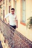 Mannstand auf Hausbalkon Macho auf moderne Hemd- und Jeansmode Mode-Modell in der Sonnenbrille auf Terrasse stockfoto