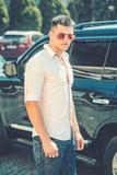 Mannstand nahe Auto auf Stadtstra?e Gesch?ftsmann in der stilvollen Sonnenbrille auf sonnigem im Freien Fahrer am Automobiltransp stockbild