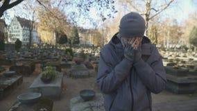 Mannstellung auf Kirchhof und tief schreien, fehlende verlorene Familie, Einsamkeit stock video