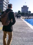 Mannstellung in der Straße trägt er Mantel und ein Rucksack und Blicke zum weißen Turm stockfotografie