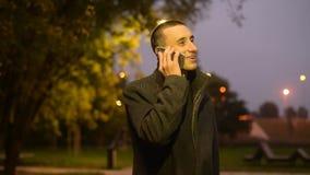 Mannstellung mit Blumen im Park im Herbst, ruft seine Freundin an, bevor sie kommt Schönes Mädchen geht auf ein Datum im Park stock footage