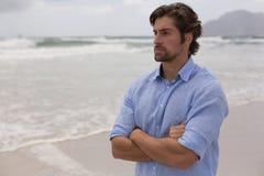 Mannstellung mit den Armen gekreuzt auf dem Strand lizenzfreies stockfoto