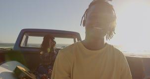 Mannstellung nahe Kleintransporter auf dem Strand 4k stock footage