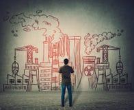 Mannstellung vor einer Betonmauer mit der unterschiedlichen Fabrik gezeichnet Kernkraftwerke, giftiger Rauch des schmutzigen Indu stockbild
