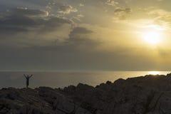 Mannstellungsabschluß das adriatische Meer in Kroatien bei dem Sonnenuntergang, der heraus Arme hält Lizenzfreie Stockfotografie