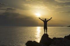 Mannstellungsabschluß das adriatische Meer in Kroatien bei dem Sonnenuntergang, der heraus Arme hält Stockbild