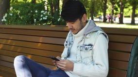 Mannstudent, der in Internet unter Verwendung des Smartphone surft stock video footage
