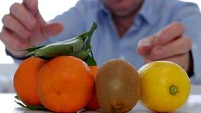 Mannstudie und die tropischen frischen Früchte anzubieten, die natürliche Vitamine empfehlen, verbrauchen stock video footage
