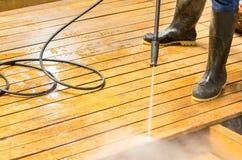 Manntragende Gummistiefel unter Verwendung des Hochwasserdrucks Stockfotografie
