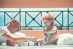 Mannunterrichtsjunge die Regeln des Schachs - spielend auf dem Boden des Balkons stockfoto