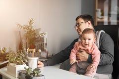 Mannvater mit Baby in der Fördermaschine, die am Büro oder am Haus mit Computer am Schreibtisch, Elternteil im Büro arbeitet stockfotos