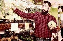 Mannverkäufer, der Blumenkohle im Gemüseshop hält Lizenzfreies Stockbild