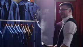 Mannverkäufer im Kostümgeschäft streift seine Jacke ab und bereitet ihn für Verkauf vor stock footage