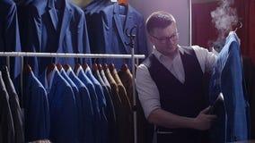 Mannverkäufer im Kostümgeschäft streift seine Jacke ab und bereitet ihn für Verkauf vor stock video