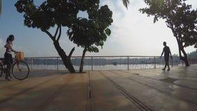 Mannweg-Mädchenfahrrad an der Seepromenade Schattenbilder stock video