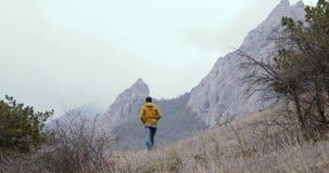 Mannweg zu den Felsen und zu den Bergen stock footage
