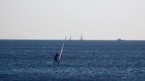 Mannwindsurfen in einem ruhigen See stock video