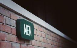 Mannzeichen auf Backsteinmauer Stockbilder