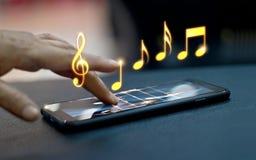 Mano abstracta que juega notas de la música sobre smartphone Imágenes de archivo libres de regalías
