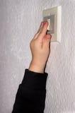 Mano activando un interruptor de la luz fotos de archivo