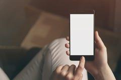Mano adolescente femenina joven usando el smatphone que se sienta en el primer de la tabla Fotografía de archivo libre de regalías