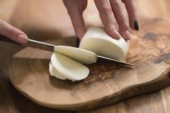Mano adolescente femenina que corta el queso de la mozzarella con el cuchillo en el tablero de madera Foto de archivo
