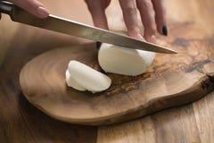 Mano adolescente femenina que corta el queso de la mozzarella con el cuchillo en el tablero de madera Fotografía de archivo