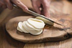 Mano adolescente femenina que corta el queso de la mozzarella con el cuchillo en el tablero de madera Fotos de archivo