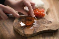 Mano adolescente femenina que corta los tomates de cereza con el cuchillo en el tablero de madera Fotografía de archivo libre de regalías