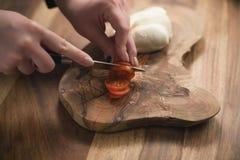 Mano adolescente femenina que corta los tomates de cereza con el cuchillo en el tablero de madera Foto de archivo libre de regalías