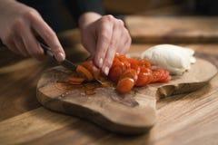 Mano adolescente femenina que corta los tomates de cereza con el cuchillo en el tablero de madera Fotos de archivo