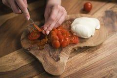 Mano adolescente femenina que corta los tomates de cereza con el cuchillo en el tablero de madera Fotos de archivo libres de regalías