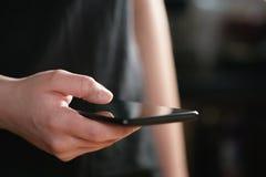 Mano adolescente femenina que sostiene el tiro del primer del smartphone Fotografía de archivo libre de regalías