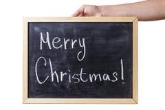 Mano adolescente femenina que sostiene la pizarra con el texto de la Feliz Navidad Imágenes de archivo libres de regalías