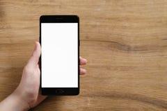 Mano adolescente femenina que sostiene smartphone con la pantalla blanca en blanco Imágenes de archivo libres de regalías