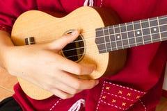Mano adolescente que juega el ukelele Imágenes de archivo libres de regalías