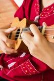 Mano adolescente que juega el ukelele Fotos de archivo