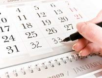 Mano, aggiungente i numeri in un calendario Fotografie Stock Libere da Diritti