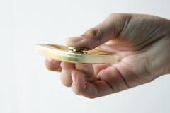 Mano aislada que hace girar al hilandero de oro de la persona agitada del metal Foto de archivo libre de regalías