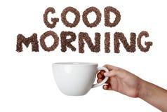 Mano aislada que sostiene la taza de café con el texto de la buena mañana Fotografía de archivo